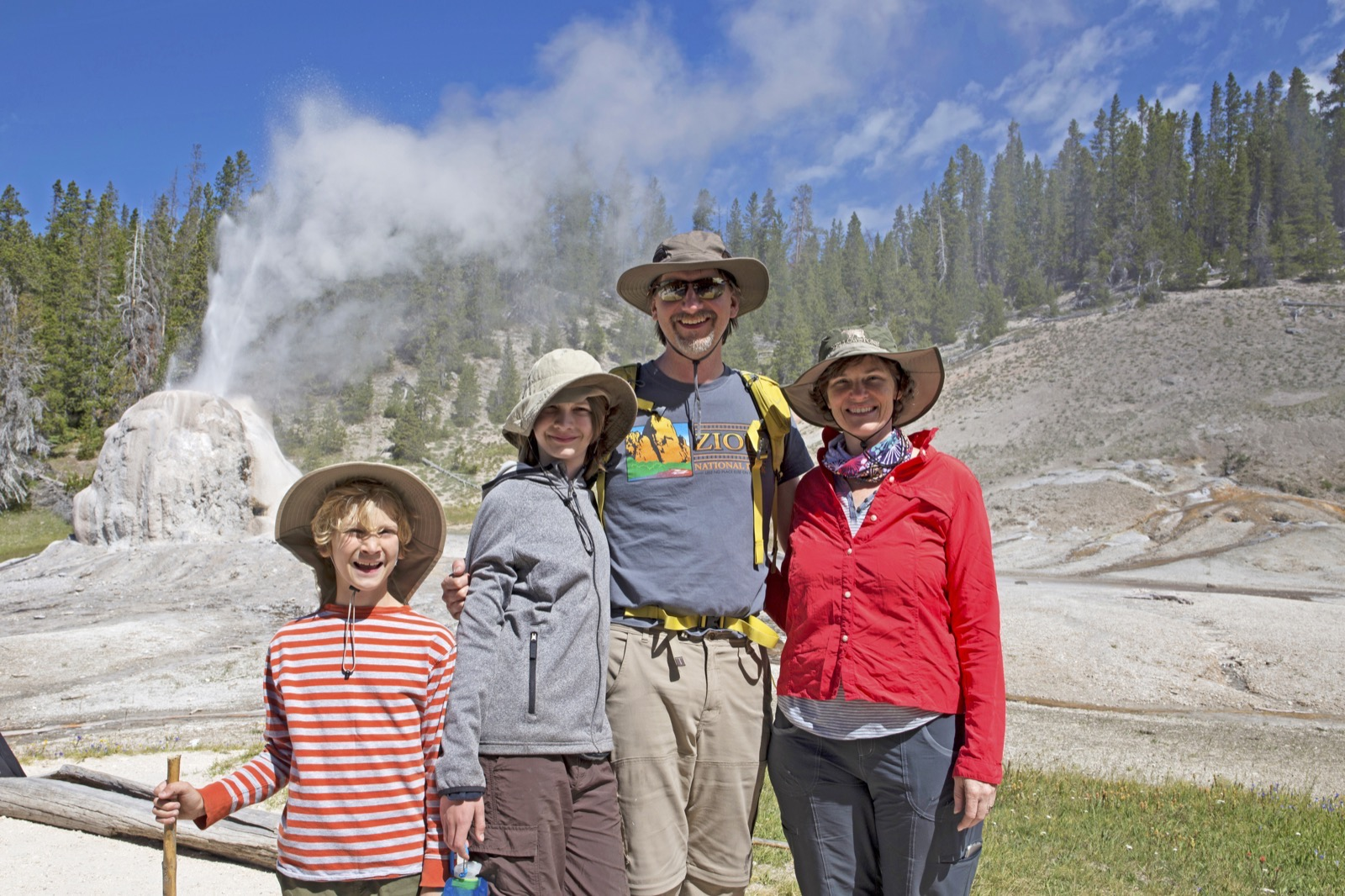 Parents and two kids stand in front of Old Faithful geyser in Yellowstone.